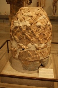 The Delphic Omphalos, c. 330 BCE, literally meaning 'navel', it is the renowned Oracle as the center of the earth. A carved stone in the form of a wicker bee-skep. Delphi Archaeological Museum, Greece.